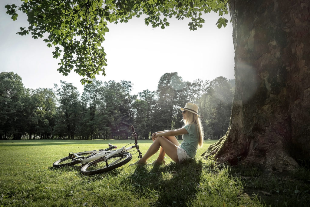 Woman sitting under sun light at day near bicycle